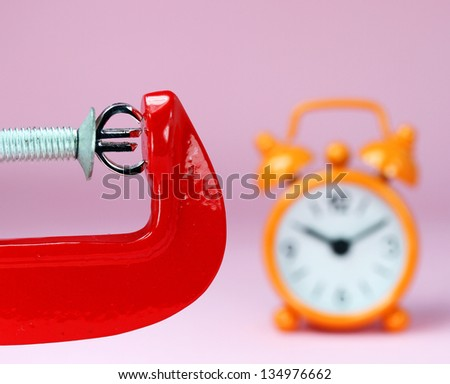 A silver Euro symbol placed in a red clamp with a pastel pink background, with an orange alarm clock in the background indicating the pressure on the Euro. - stock photo