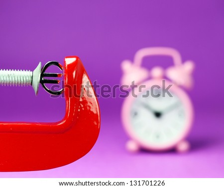 A silver Euro symbol placed in a red clamp with a purple background, with a pink alarm clock in the background indicating the pressure on the Euro. - stock photo