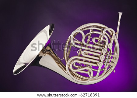 A silver French horn isolated against a spotlight purple background.