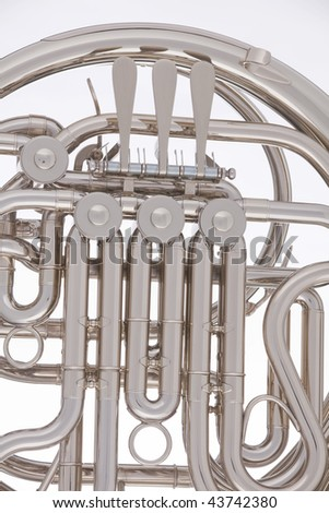 A silver French horn isolated against a white background in the vertical format. - stock photo