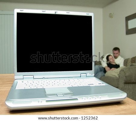 A silver laptop on a wood table with a blank screen ready for your copy.   Very shallow DOF, focus is on the screen itself, the man and the woman in the background are very out of focus.