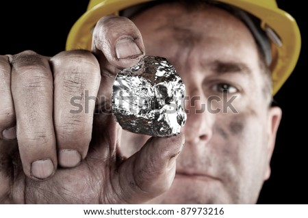 A silver miner shows off his newly excavated silver nugget. - stock photo