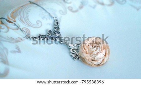 a silver necklace with a real rose in a jewelry resin