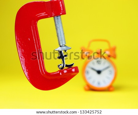 A silver Pound symbol placed in a red clamp with a yellow background, with an orange alarm clock in the background indicating the pressure on the pound sterling.