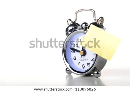 a silver retro alarm bell with paper notice on white background - stock photo