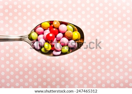 a silver spoon filled with edible decorations for cupcakes - stock photo