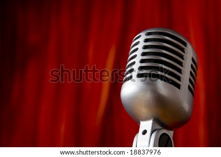 A silver vintage microphone in front of a red stage curtain with copy space