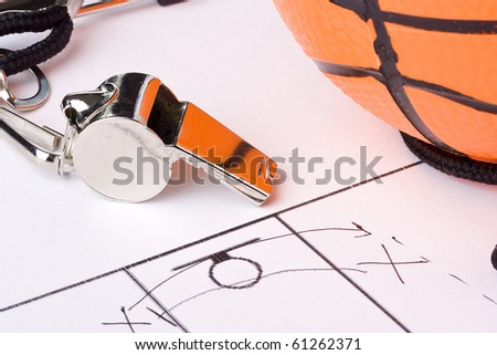 A silver whistle laying next to an orange basketball and the drawing of a game plan. - stock photo