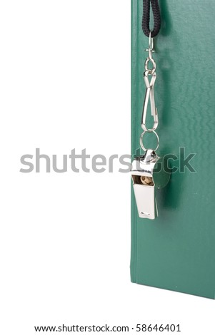 A silver whistle placed on the coaches green playbook. - stock photo