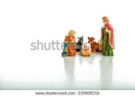 A simple Christmas Crib where the little statues represent the Holy Family, the Virgin Mary, Saint Joseph and the infant Jesus, watched by ox and donkey during the night of the 25th of December - stock photo