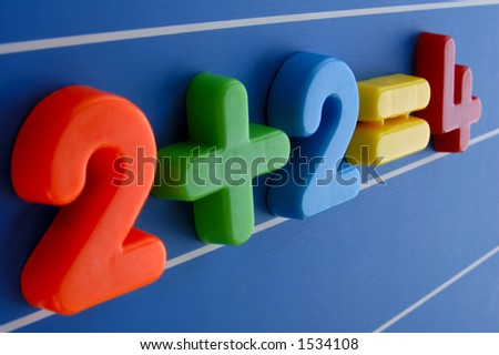 A simple equation, from a child's toy number set, looms large and intimidating. Is this what a sum looks like to a child having difficulty with maths? Focus on the plus sign. - stock photo