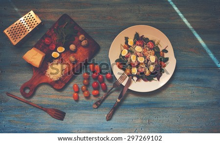 A simple recipe salad of fresh greens, quail eggs and cherry tomatoes, filling may be different, to serve the salad on a large white plate, side by side on a wooden board is grated parmesan cheese - stock photo