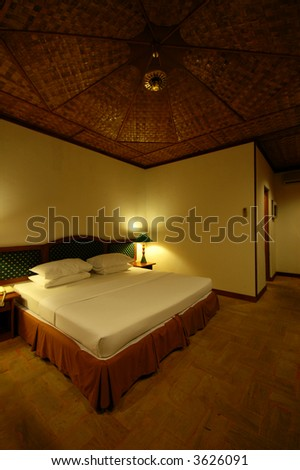 A simple room with a nice plush bed - stock photo