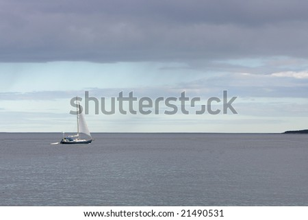 a simple sailboat sailing in the blue ocean during a stormy day