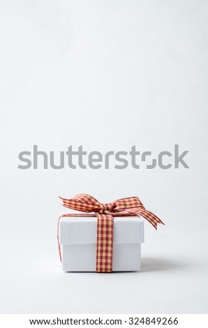 A simple, small white lidded gift box, closed and tied to a bow with a red gingham checked ribbon on plain background. - stock photo
