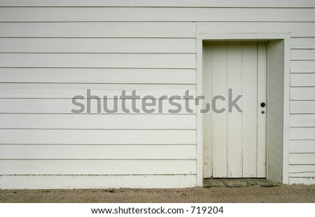 A simple white doorway on the side of an old wooden house.