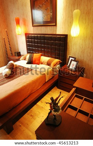a simply decorated bedroom in warm browns - stock photo