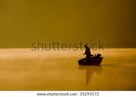 A single angler enjoys fishing from a boat on a beautiful morning. - stock photo