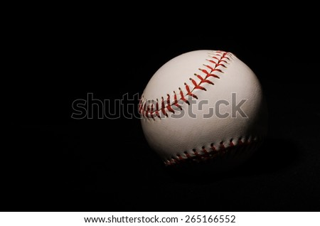 A single baseball on a black backdrop with single light illuminating it for isolation and drama.