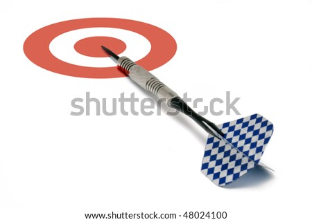 A single blue and white finned dart laying on a red and white bull's-eye target.  Conceptual business image for being 'on target', 'moving forward', etc. - stock photo