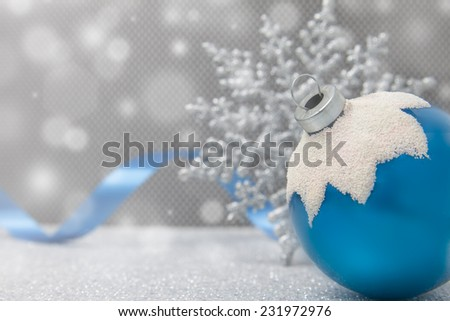 A single blue Christmas snow-capped ornament sits with a snowflake and ribbon on a glittery surface - stock photo