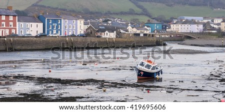 A single boat, in Aberaeron harbour, on the west coast of Wales
