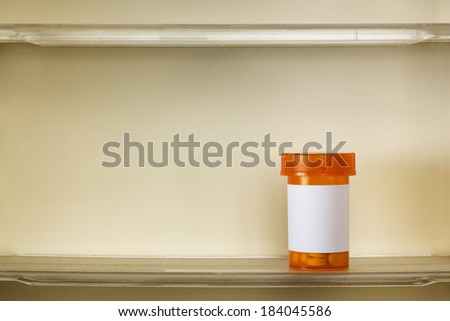 A single bottle of medicine on the shelf of a 1960's medicine cabinet. - stock photo