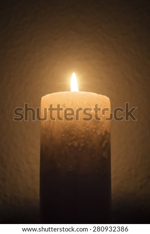 A single candle burns brightly in dark room - portrait interior - stock photo