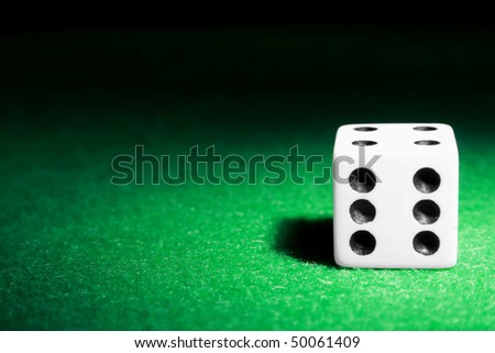 A single die laying on a green felt table - stock photo
