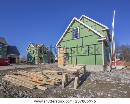 A single family home under construction in a housing development complex. - stock photo