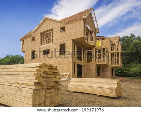 A single family home under construction. The house has been framed and covered in plywood - stock photo