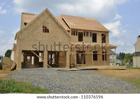 A single family home under construction.  The house has been framed and covered in plywood.  There is a two car garage with a gravel driveway. - stock photo