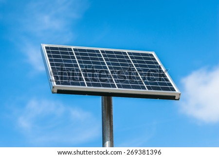 A single, freestanding solar panel isolated against a blue sky.