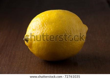 A single fresh yellow lemon on a wood grain table against a black background. - stock photo