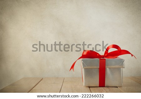 A single gift box wrapped in silver paper and tied to a bow with red satin ribbon.  Placed on a wood plank table with parchment background. Vintage style. - stock photo