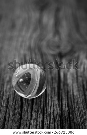 A single glass marble on a wooden floor in black and white. - stock photo
