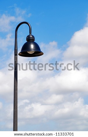 A single hooded street light with blue sky background - stock photo