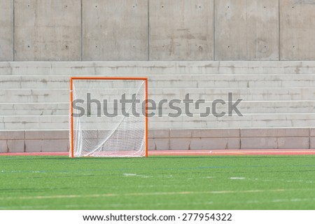 A single lacrosse goal on a turf field with a cement wall background - stock photo