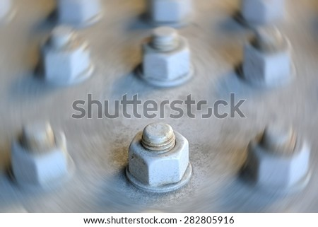 A single large nut and bolt in focus surrounded by blurred other nuts and bolts  - stock photo