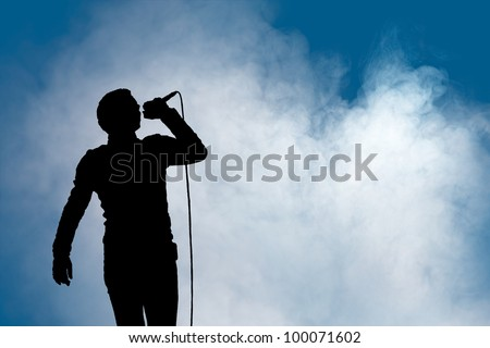 A single man sings into a microphone at a concert with atmospheric foggy background for copyspace - stock photo