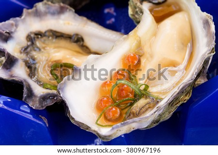 A single oyster live with garnish with an oyster shuck in the foreground with salmon roe. - stock photo