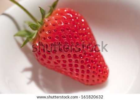 A single red strawberry sitting on a white bowl. - stock photo