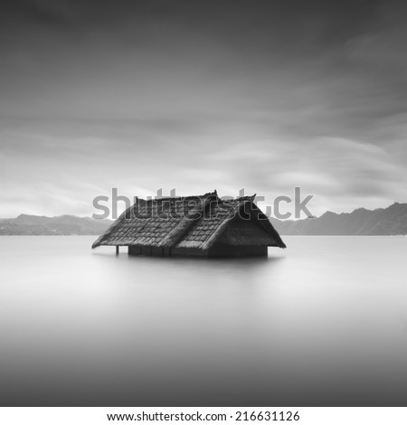 A single sunk house in the water . long exposure black and white ( image has contain grain or noise ) - stock photo