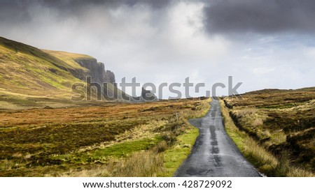 A single track country lane runs through moorland under the Quiraing mountain on Scotland's Isle of Skye.