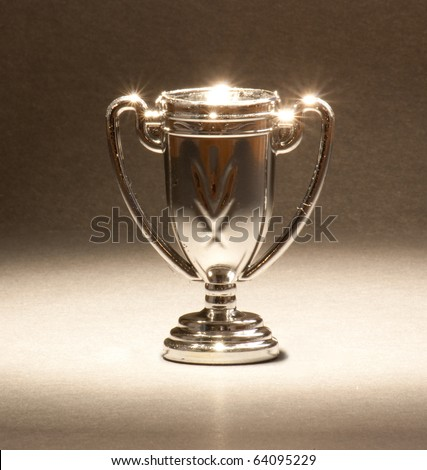A single trophy shining under lights. - stock photo