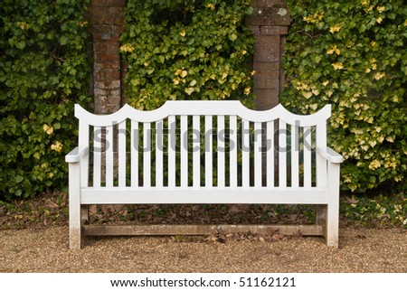 A Single White Bench In Front Of An Ivy Covered Brick Wall