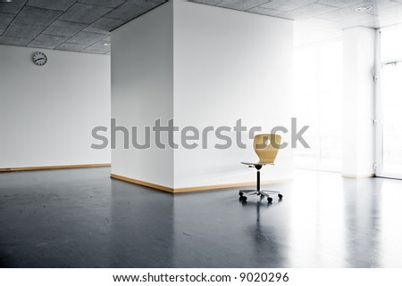 a single wooden chair in a bright empty room with a wall clock and sunlight and sunbeams shining from outside - stock photo