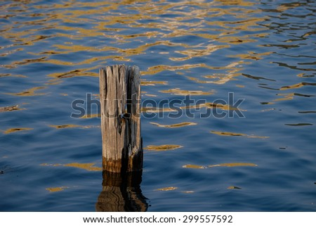 A single wooden piling at sundown - stock photo