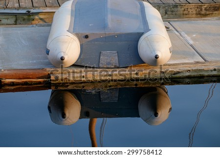 A single zodiac pontoon boat sits upside down on the deck of a harbor at sunset - stock photo