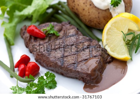 a sirloin strip steak with vegetables and savory sauce